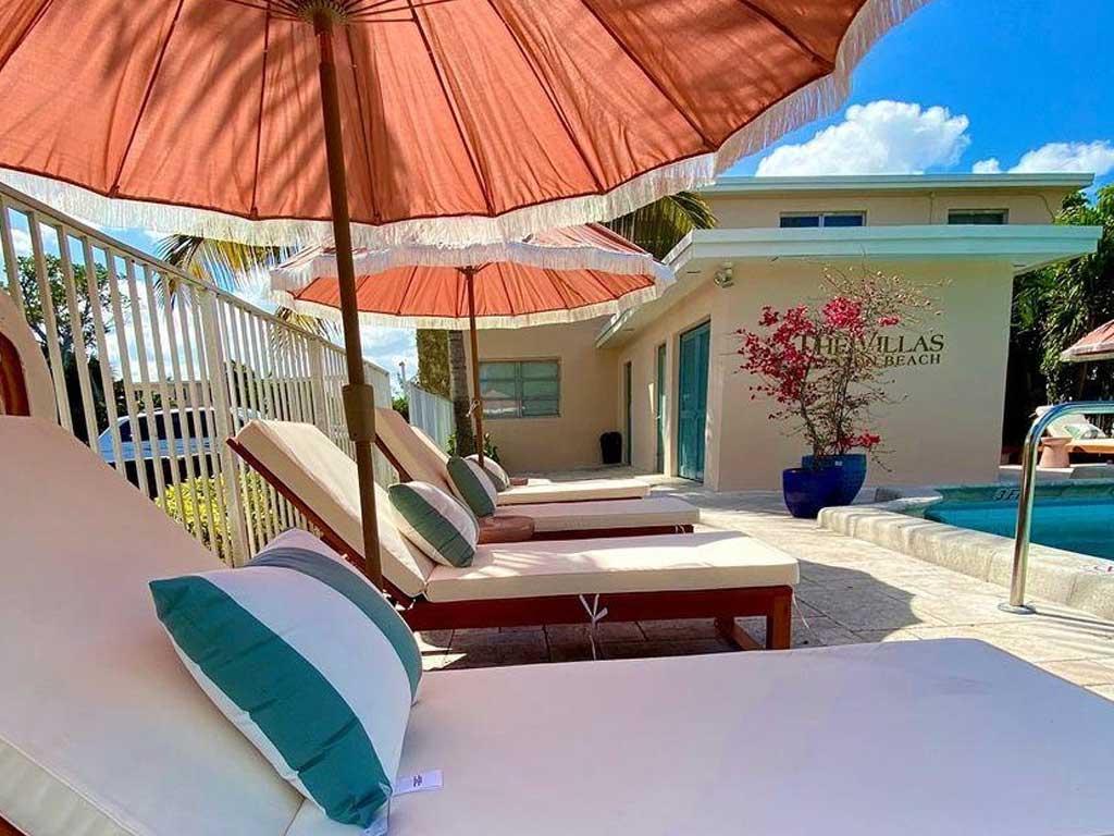 The Villas at Boynton Beach exterior pool lounge chairs and umbrellas