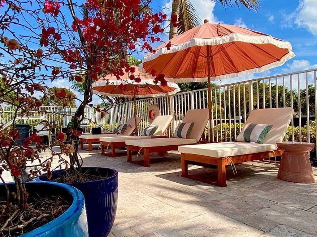 The Villas at Boynton Beach pool lounge chairs and umbrellas